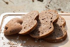 Several slices of Bread wheat and wooden chopping board Royalty Free Stock Image