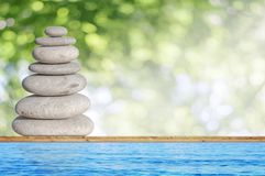 Several small beach stone like symbol of balance on wood. With zen stones Stock Photo