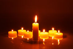 Several small candles in a row. Dark background. Several small candles in a row and one big in the foreground Royalty Free Stock Photography
