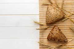 Several small multi grain triangular shaped bread sprinkled with whole sunflower seeds, flax and sesame seeds and wheat and barley Stock Photography