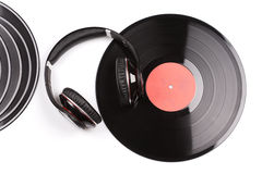 Several small and one big black vinyl records beside elegant headphones. Royalty Free Stock Images