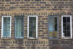 Several small vintage windows in a brick antique wall. Street photo stock images