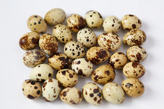 Several small yellow quail eggs lie on a white background Stock Photo