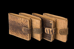 Several of snake skin purse on a black background. Several brown purse made of snake skin on a black background Royalty Free Stock Images