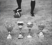 Several soccer trophies against football player. Stock Photo