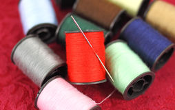 Several spools of thread with a sewing needle Stock Photography