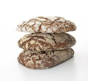 Several stacked artisan loaves viewed frontally on a white background. Several stacked rye artisan breads viewed frontally on a white background stock image