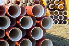 Stack of sewer pipes. Several stacks of brown sewer pipes on the grass stock image