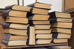 Several stacks of large old books lying on the table stock photo