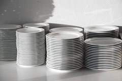 Several stacks of white porcelain plates Stock Photos