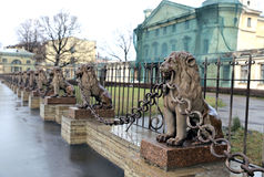 Several statues of bronze lions along the fence Stock Image