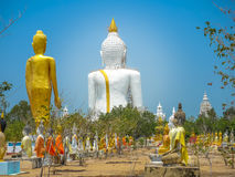 Several statues of Buddha posture. Big white Buddha statue in front of Royalty Free Stock Photography