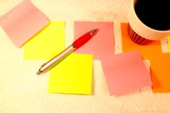 Coffee cup, sticky notes and a ballpoint pencil on white lace surface royalty free stock image