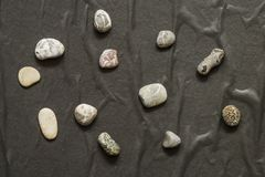 Several stones in a chaotic manner lie on a dark background stock photo
