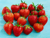 Several strawberries. Few ripe strawberries on a blue background Royalty Free Stock Photography