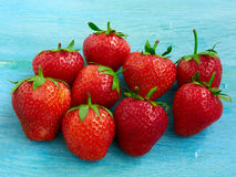 Several strawberries. Few ripe strawberries on a blue background Royalty Free Stock Photo