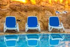 Several of sun loungers by a beautiful swimming pool Stock Images