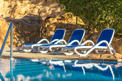Several of sun loungers by beautiful swimming pool and treess. Royalty Free Stock Images