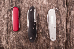 Several swiss army knifes on wood in the. Swiss army knife in the jungle Stock Image