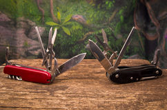 Several swiss army knifes on wood in the. Swiss army knife in the jungle Royalty Free Stock Image