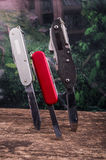 Several swiss army knifes on wood the rainforest Stock Photo