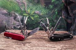 Several swiss army knifes on wood the rainforest. Several swiss army knifes on wood in the rainforest Royalty Free Stock Image