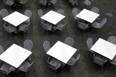 Several tables and chairs ready for diners to settle in for a meal Royalty Free Stock Images