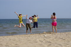 Several taking photo girls on the beach. A girls is taking photograph  for three jumping girls on sandy beach Royalty Free Stock Photos