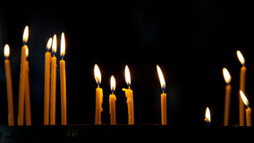 Several tall candles lit in a church Royalty Free Stock Image