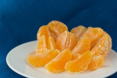 Several tangerines on white plate. Several peeled tangerines on white plate with blue linen background Royalty Free Stock Photos