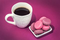 Several tasty pink macaroons in bowl and coffee stock images