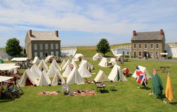 Several tents set up on lawn with stone buildings beyond, Fort Ontario, New York, 2016 Stock Photo