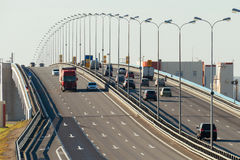 Several trucks and cars driving on the highway. In the afternoon stock photo