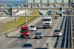 Several trucks and cars driving on the highway. In the afternoon stock image