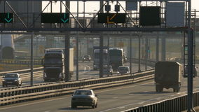 Several trucks and cars driving on the highway at the sunset. Saint-Petersburg, Russia, 2016. Several trucks and cars driving on the highway in the afternoon stock footage