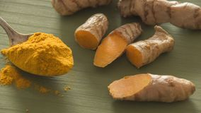 Turmeric roots on wooden surface. Several turmeric roots and a spoon with turmeric powder on a wooden surface Stock Images