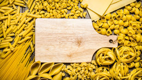 Several types of dry pasta and spaghetti with empty wooden board. Stock Photos
