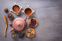 Several types of green tea, black tea, hibiscus tea and tea ceremony attributes - a ceramic teapot, cups, a strainer, chopsticks. And tweezers are placed on an royalty free stock image