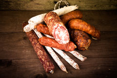 Several types of sausages on a wooden background Stock Photos