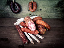 Several types of sausages on a wooden background.tinted Stock Image
