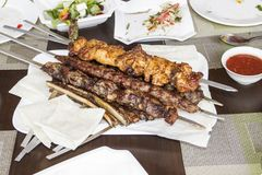 Several types of shish kebab, vegetable salads and seasoning. stock images