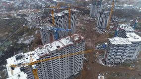 Several unfinished buildings with cranes nearby. Several unfinished apartment buildings with two or three tower cranes near them stock video footage