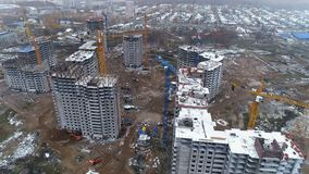 Unfinished apartment buildings covered by snow. Several unfinished residential buildings with working people in circular view stock footage