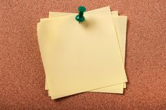 Several untidy sticky post notes pinned to cork board Stock Image
