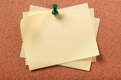 Several untidy yellow sticky post notes pinned to cork board background Royalty Free Stock Image