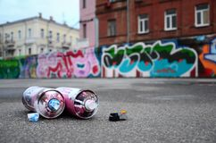 Several used spray cans with pink and white paint and caps for s royalty free stock photo