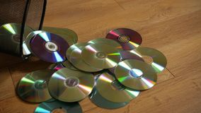 Several useless digital discs falling out of the dustbin. stock footage