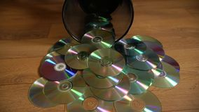 Several useless digital discs falling out of the dustbin. Conceptual slow motion footage for technology development stock video footage