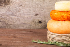Several varieties of cheese and a sprig of rosemary on an old wo Royalty Free Stock Photo