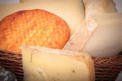 Several varieties of cheese in a wicker basket Royalty Free Stock Photography